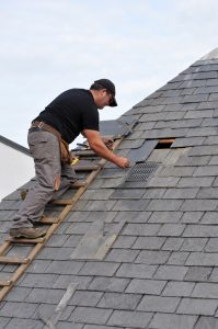 roof repair image showing a man fixing the roof